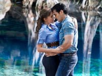 Angelique Boyer y David Zepeda en una escena de la telenovela Abismo de Pasión. Abrazo romántico al lado de una laguna azul.