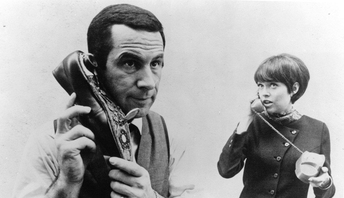 Super Agente 86, sus protagonistas Don Adams  escuchando por un teléfono en su zapato y Barbara Feldon escuchando en un teléfono real.