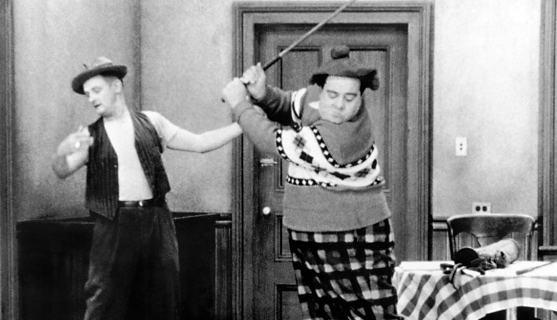 Art Carney enseñándole a jugar golf a Jackie Gleason en la película The Honeymooners