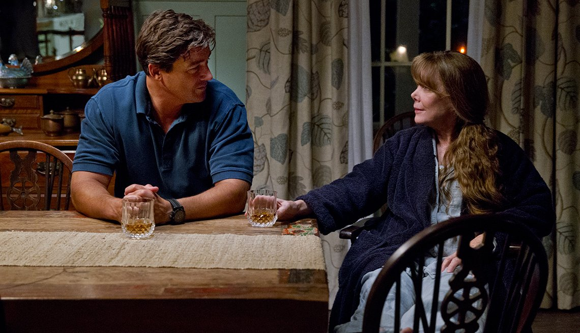 Kyle Chandler and Sissy Spacek sitting at a kitchen table sharing a drink in 'Bloodline'