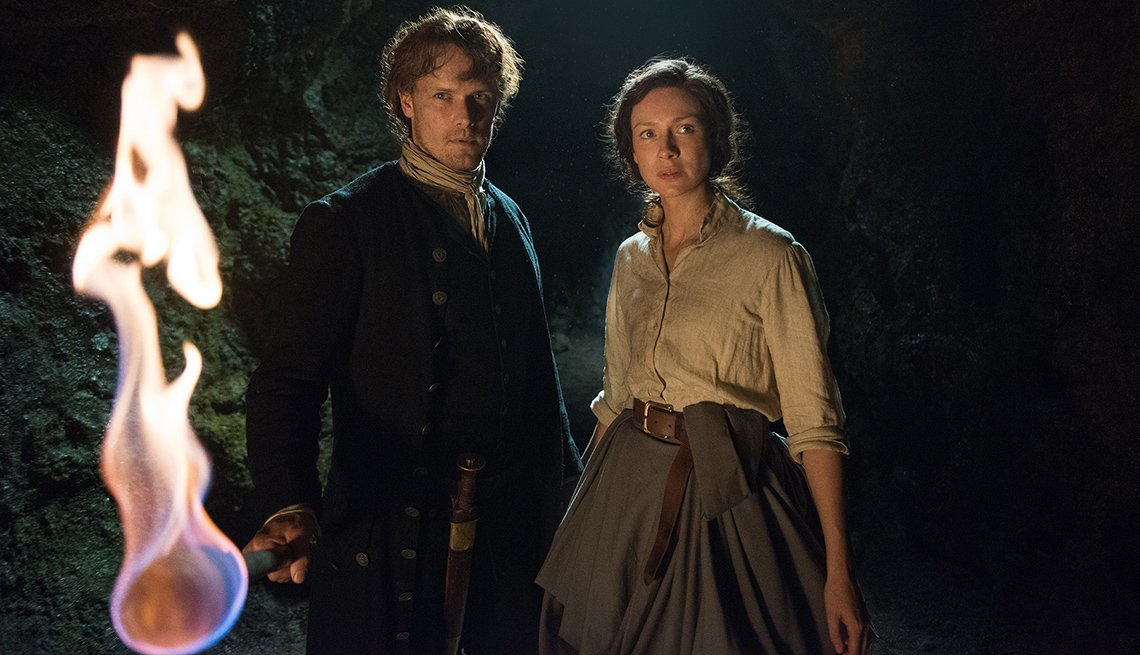 Sam Heughan as Jamie Fraser and Caitriona Balfe as Claire Randall, in Scottish costume holding torch in 'Outlander'