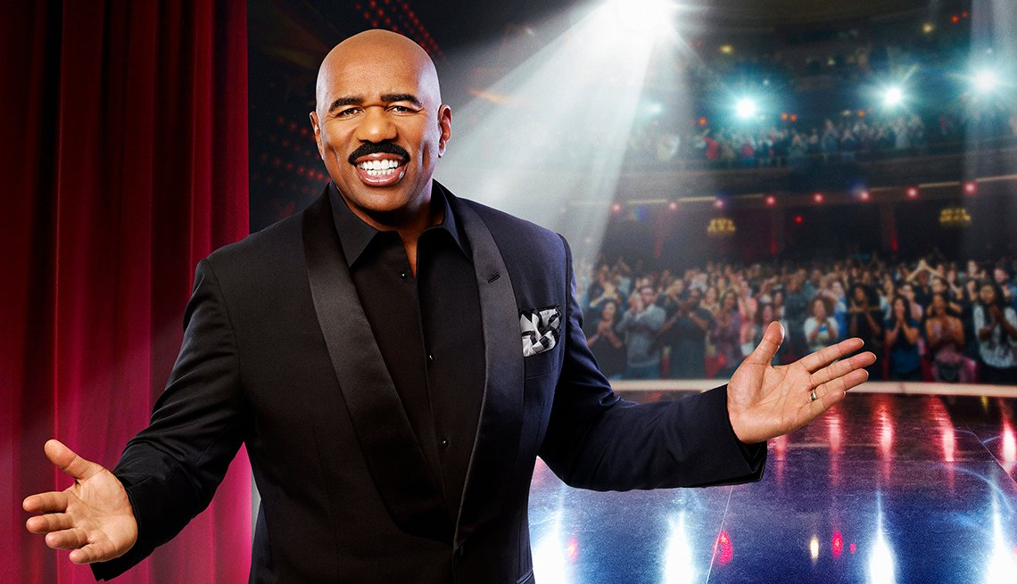 portrait of steve harvey with arms outstretched on a stage with audience behind