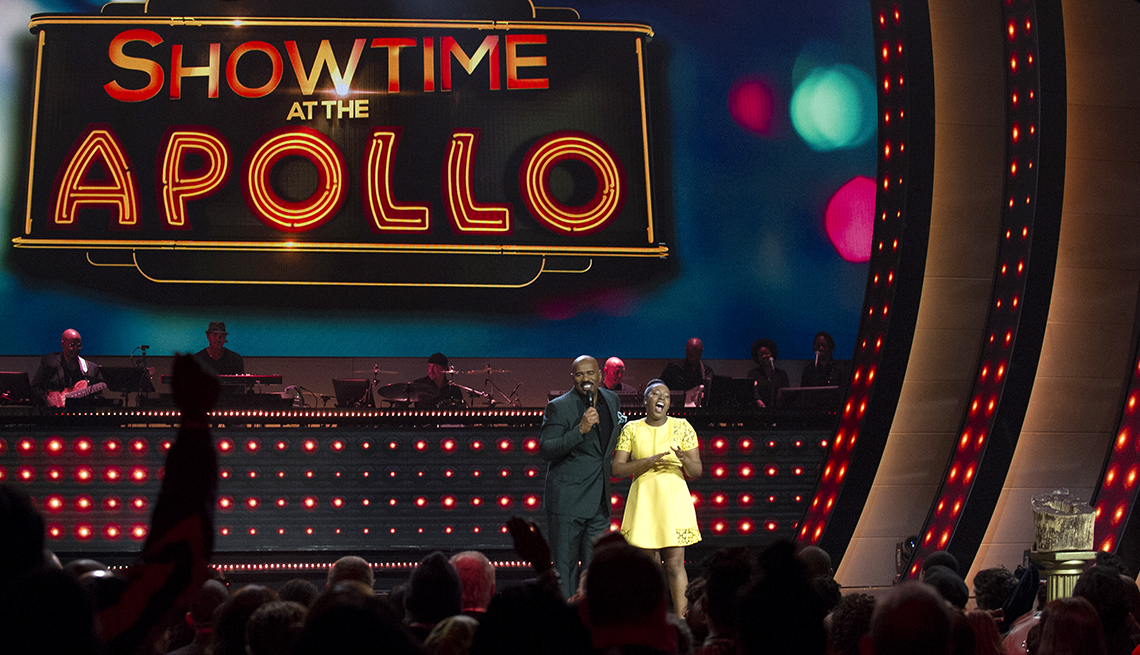 steve harvey on stage with young woman in yellow dress
