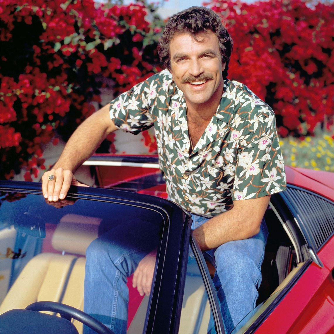 Tom Selleck wears a floral shirt and sits in a red Ferrari in 'Magnum, P.I'