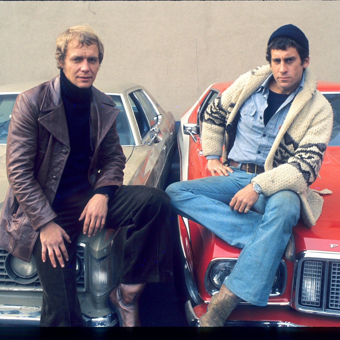 David Soul and Paul Michael Glaser pose on the hood of cars in 'Starsky and Hutch'