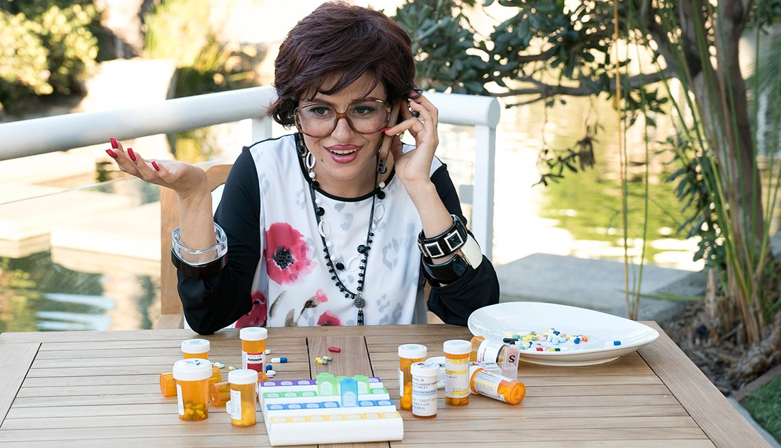 A woman sitting at a table with pill bottles on a table in front of her.