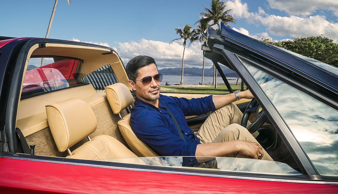 Jay Hernandez sits in a red convertible near the ocean, palm trees are seen in the distance.