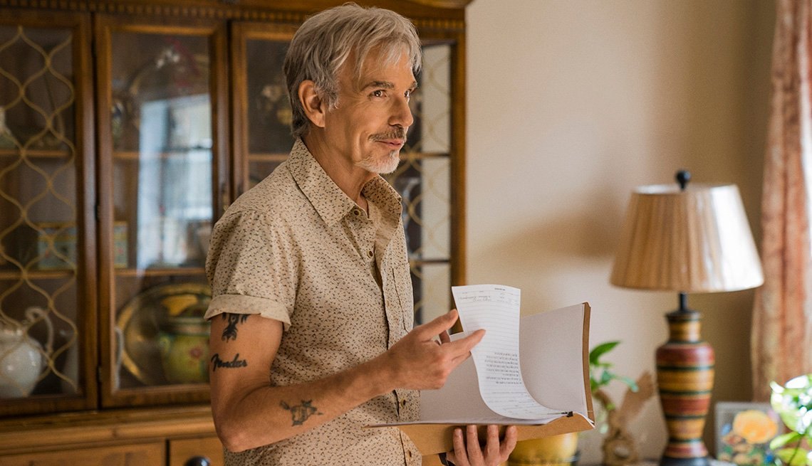 Billy Bob Thornton in character, standing in a living room holding a paper.