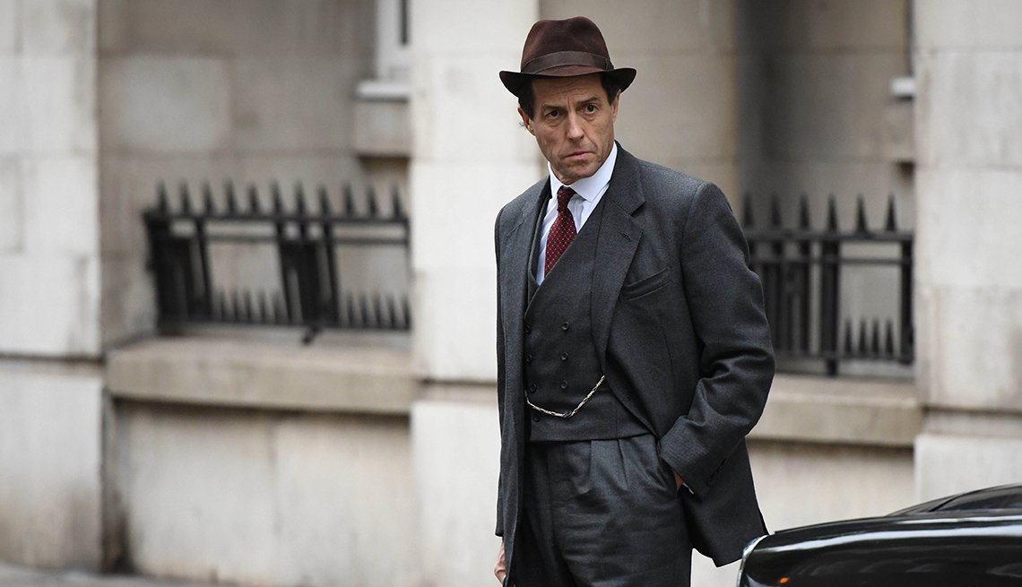 Hugh Grant dressed in a suit, wearing a hat.
