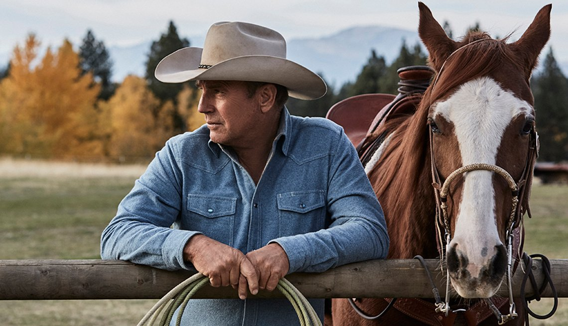 Kevin Costner wearing a cowboy hat and standing in front of a horse, leaning on a fence.