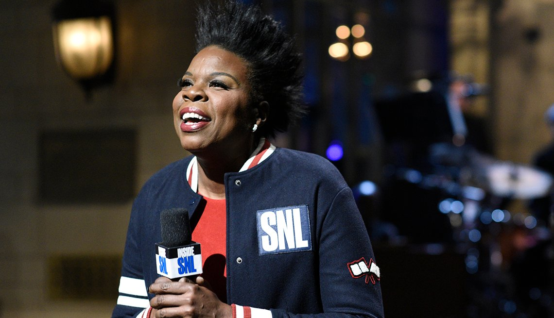 """Leslie Jones wearing an SNL jacket and holding a microphone during an opening monologue on """"Saturday Night Live"""""""