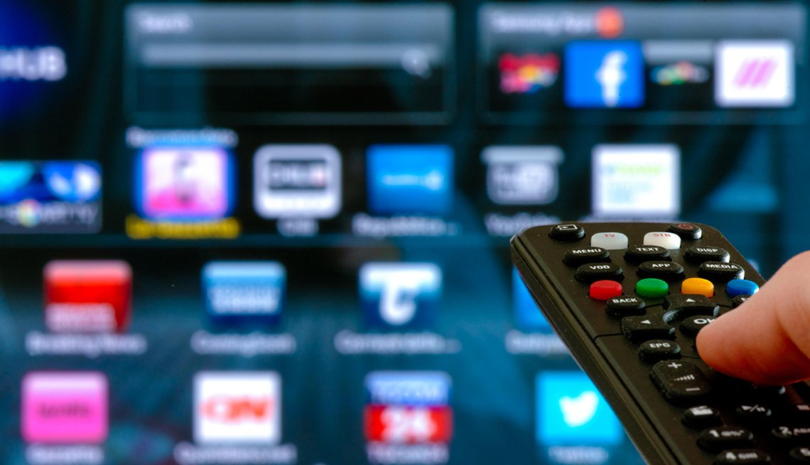Pantalla de televisor al fondo y un dedo sobre un control remoto