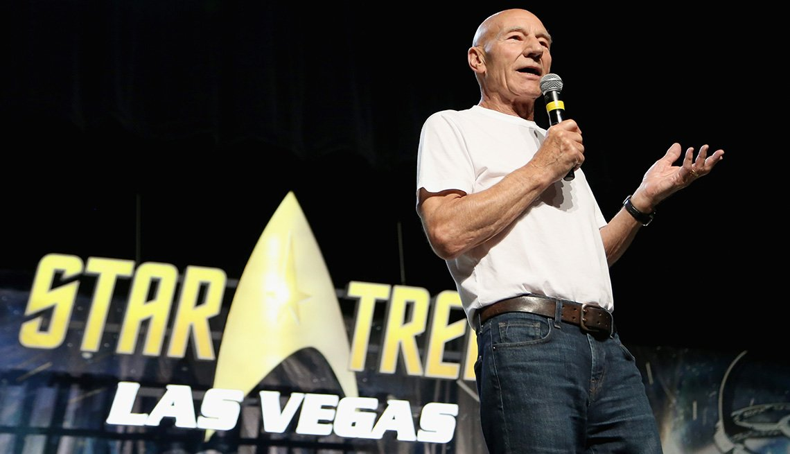 """Patrick Stewart standing on stage with a sign behind him that reads """"Star Trek Las Vegas.:"""