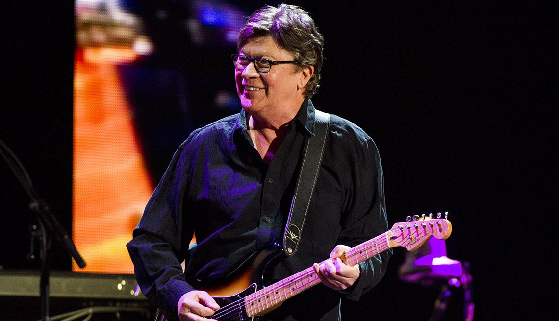 Robbie Robertson on stage holding a guitar