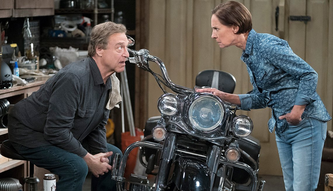 John Goodman and Laurie Metcalf standing over a motorcycle in a scene from
