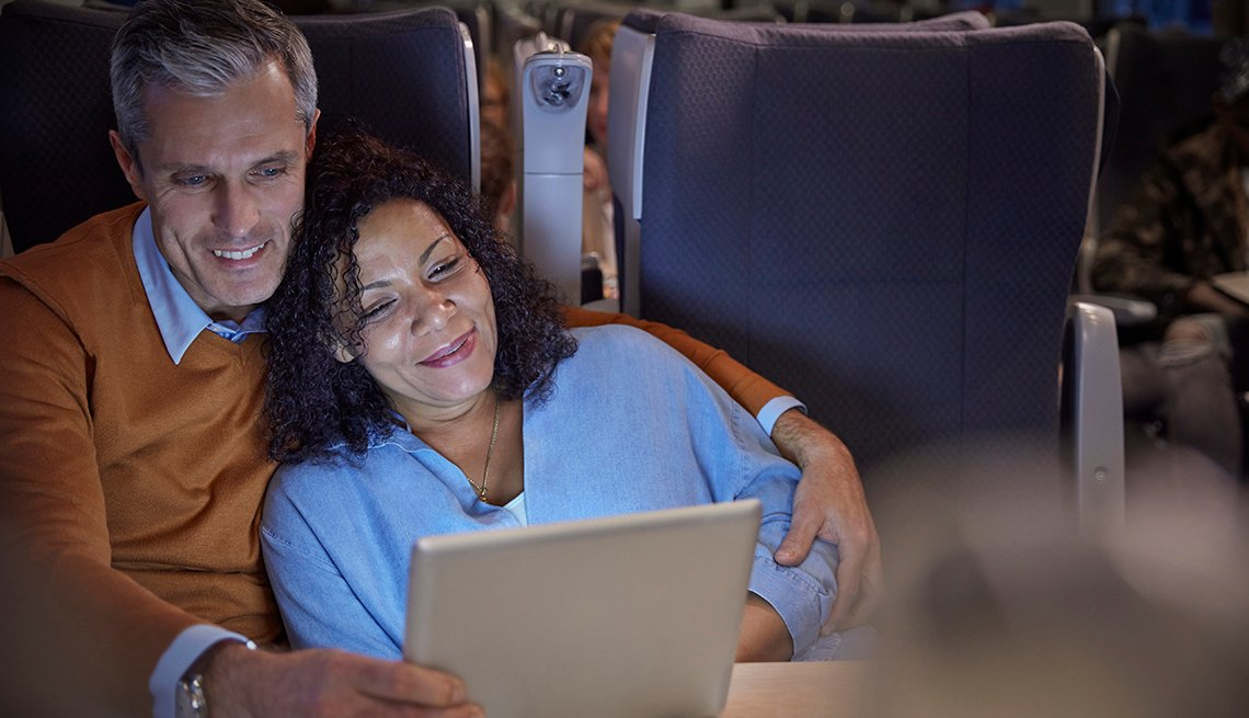 A couple sits together on a plane while streaming their favorite tv show on a tablet device