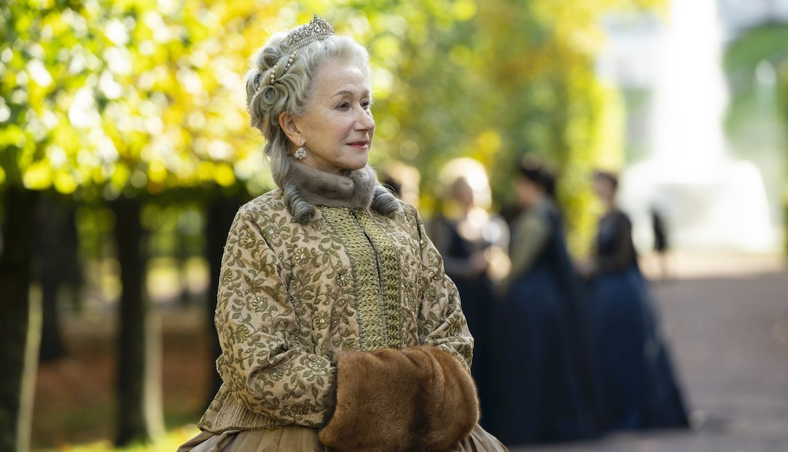 Helen Mirren stands outside in a heavy coat, crown and hand muff in 'Catherine the Great'