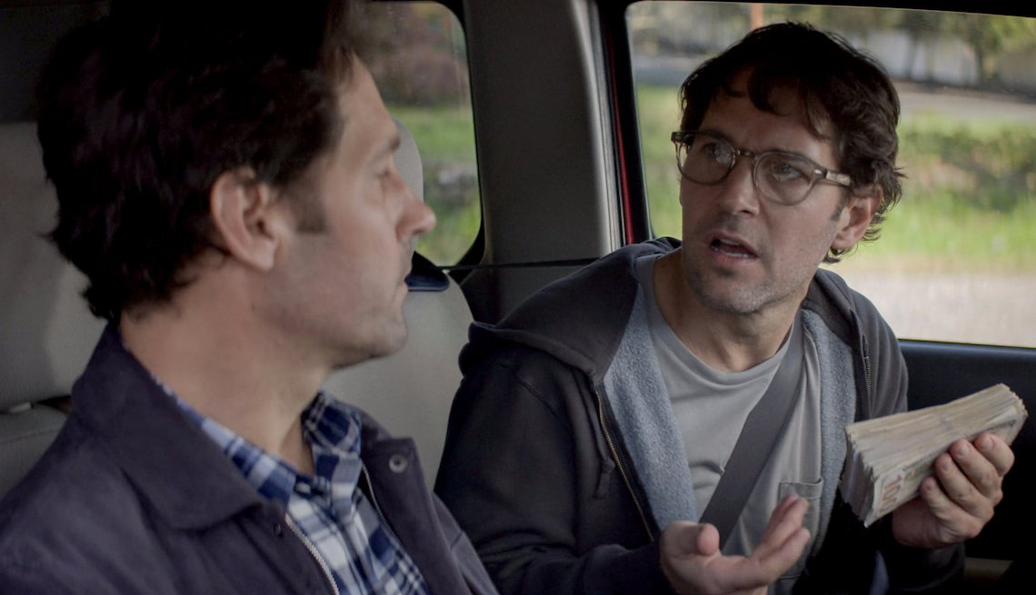 A scene inside a car, Paul Rudd holds money while talking to Paul Rudd in the limited Netflix series 'Living with Yourself'