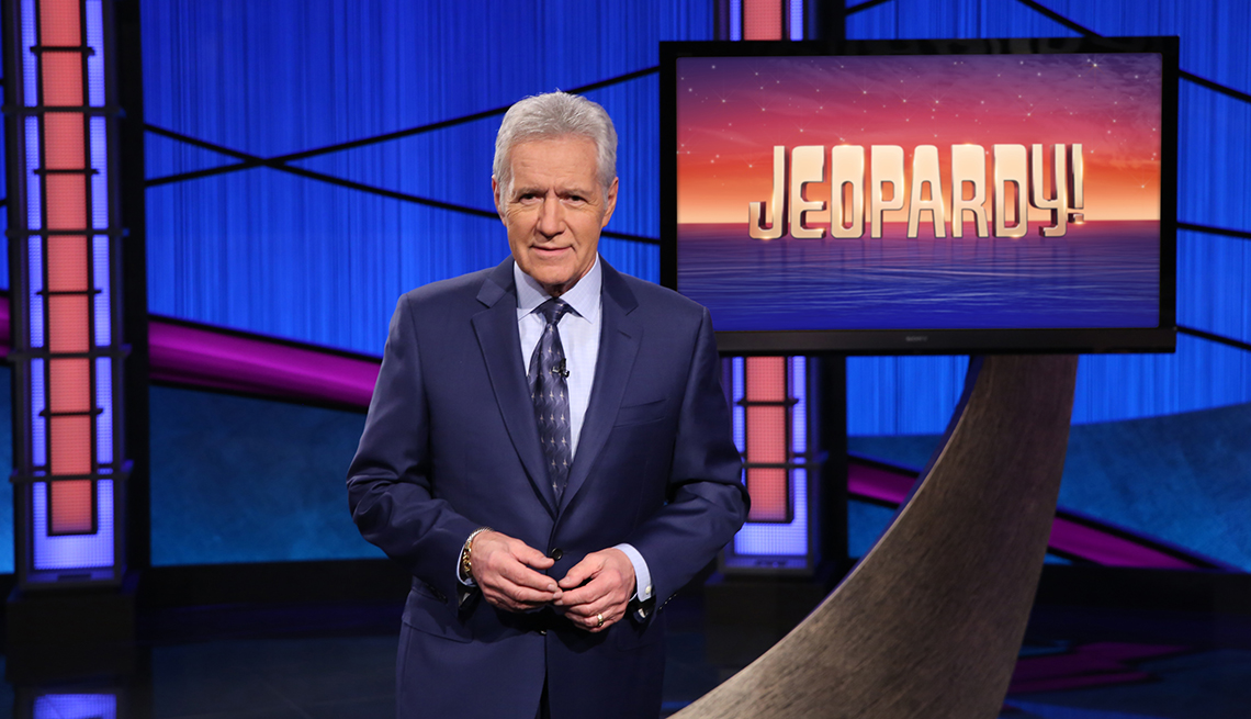 Alex Trebek in a studio standing in front of a Jeopardy monitor