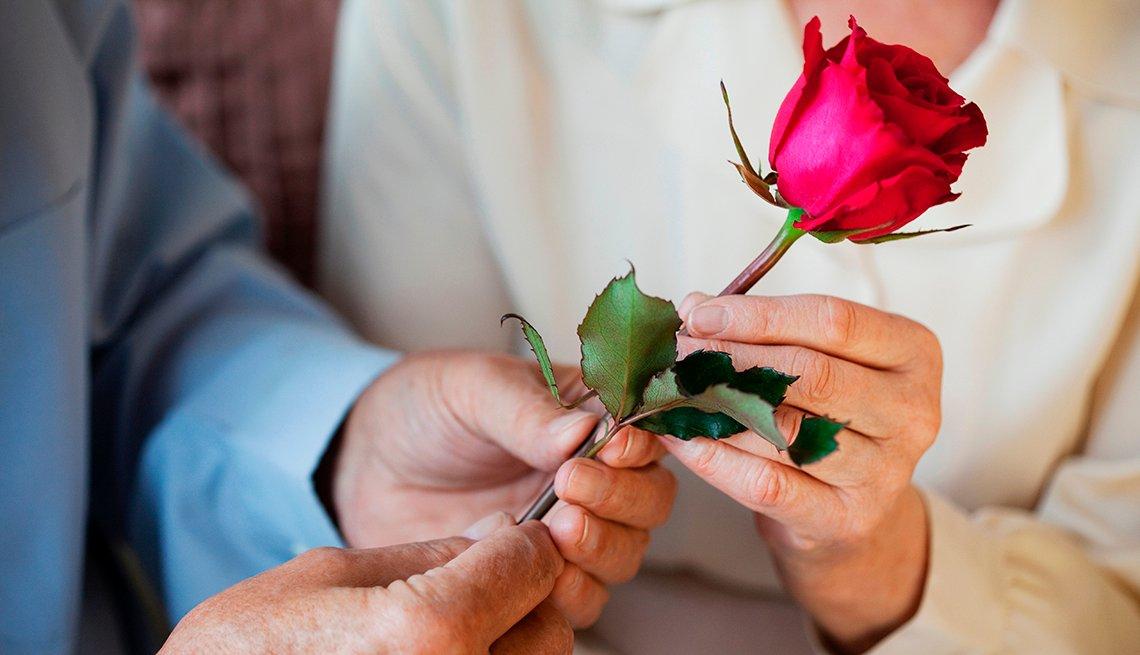 Hombre y mujer sostienen una rosa en sus manos.