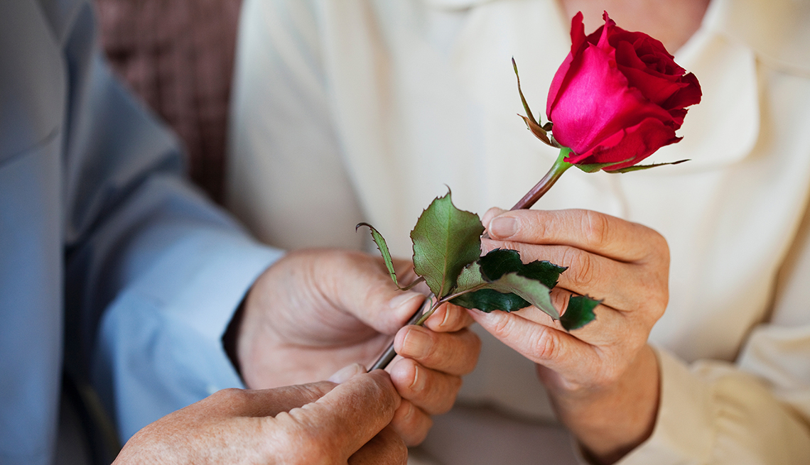 A man handing a rose to a woman