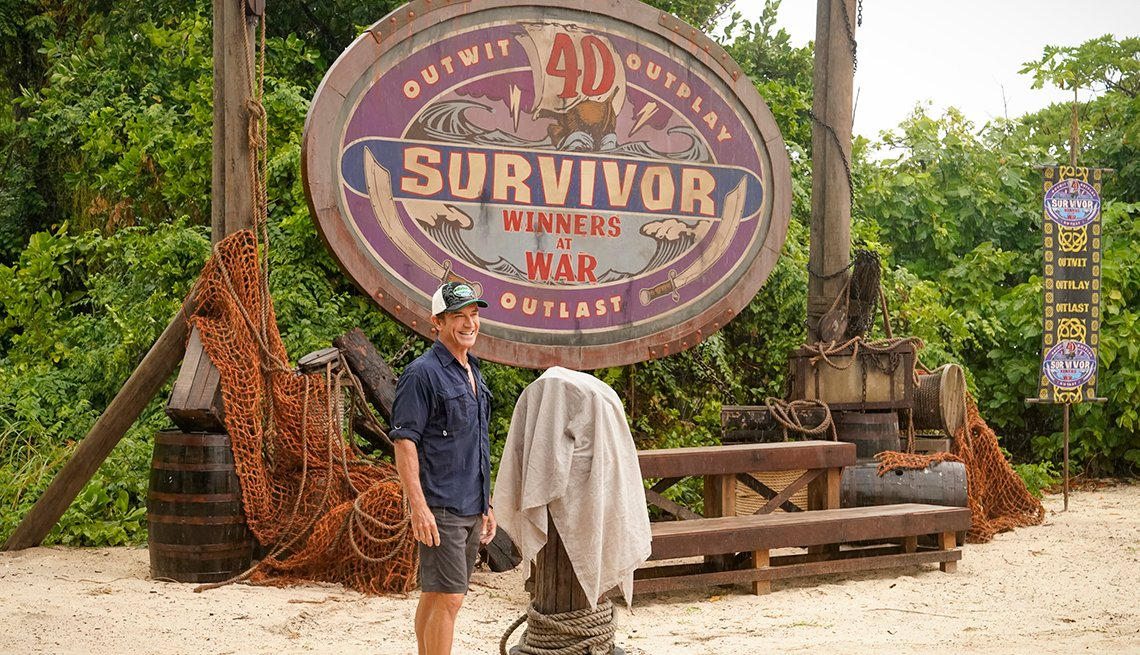 Jeff Probst in front of a sign on a beach as he hosts Survivor Winners at War the 40th season of the television reality series