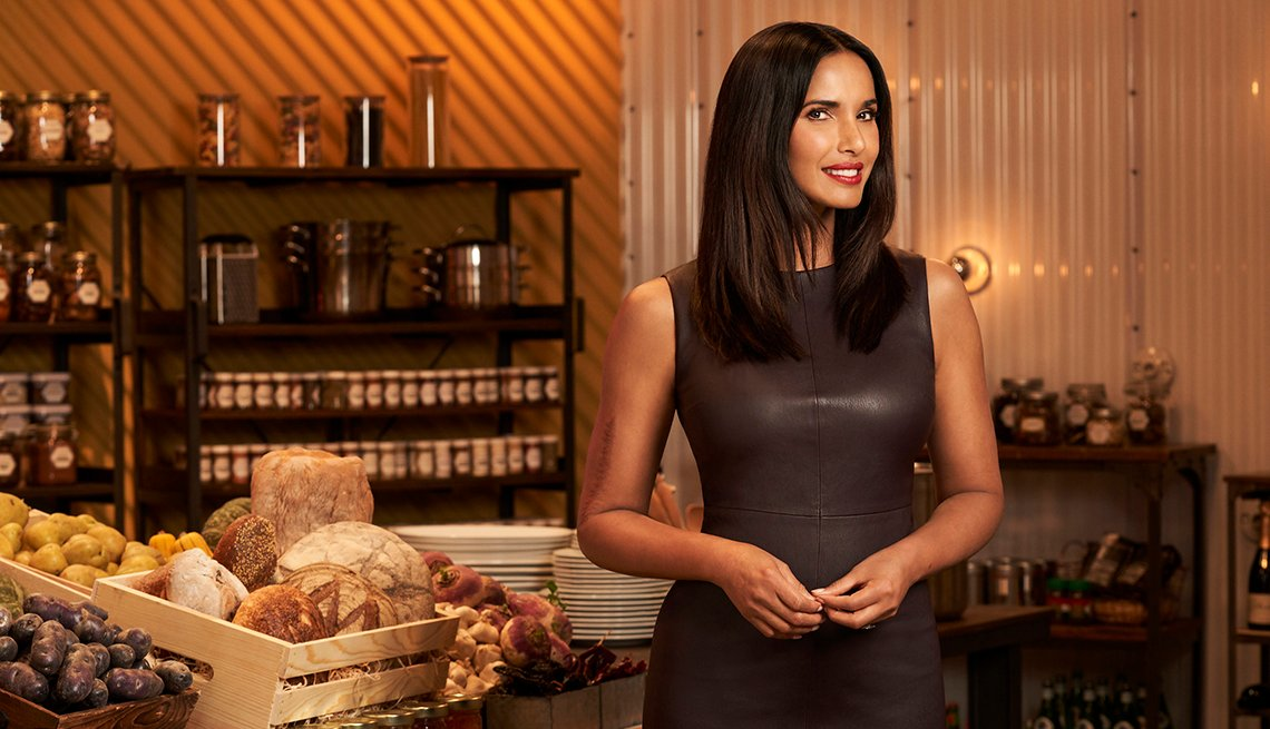 Top Chef host Padma Lakshmi next to baskets of bread and other assorted food