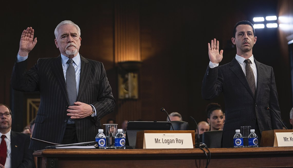 Brian Cox as Logan Roy and Jeremy Strong as Kendall Roy raise their hand in the courtroom in the H B O show Succession