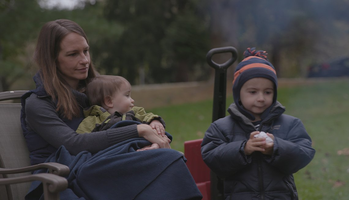 Cheryl Yoder and two of her sons sit by a fire in their yard