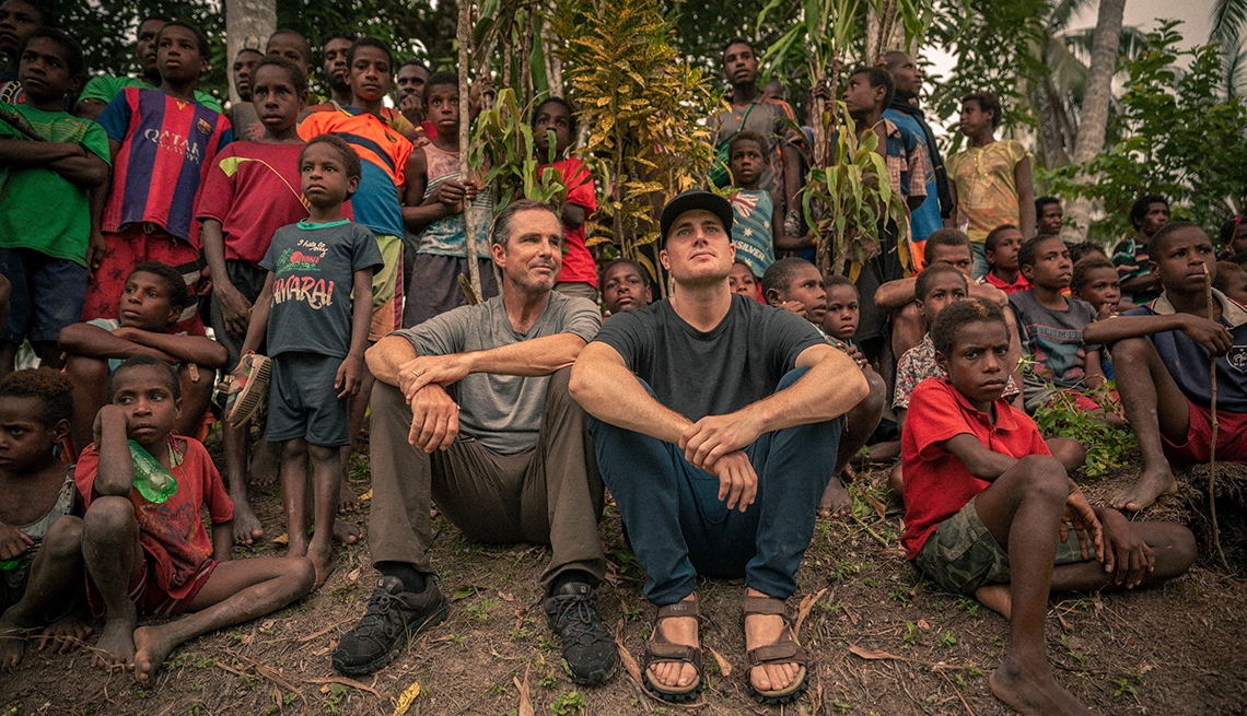 Bob and Mack Woodruff watch a traditional archery competition in Papua New Guinea with the village children