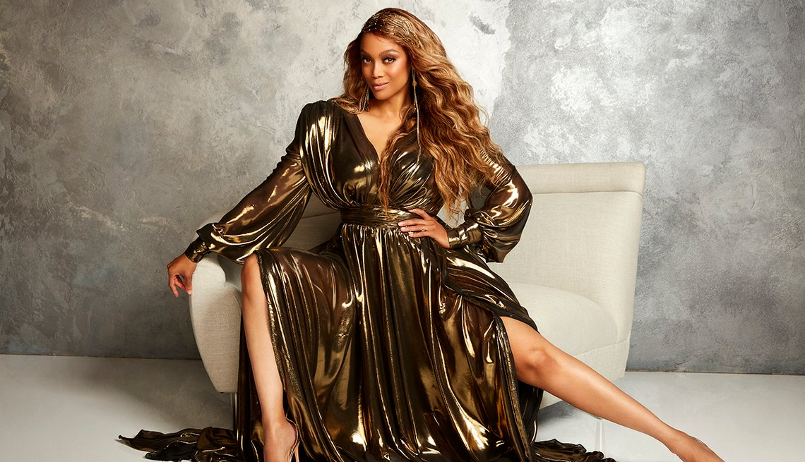 Dancing with the Stars host Tyra Banks wearing a dark gold dress poses for a photo in a chair