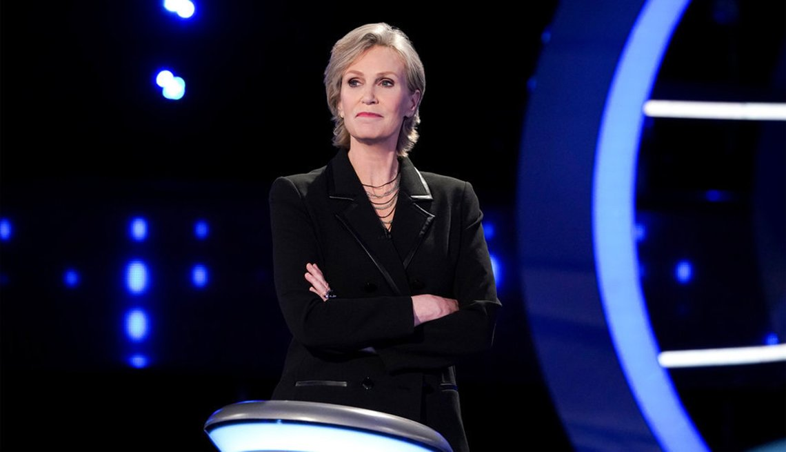 Jane Lynch stands at the podium as the host of the NBC show Weakest Link