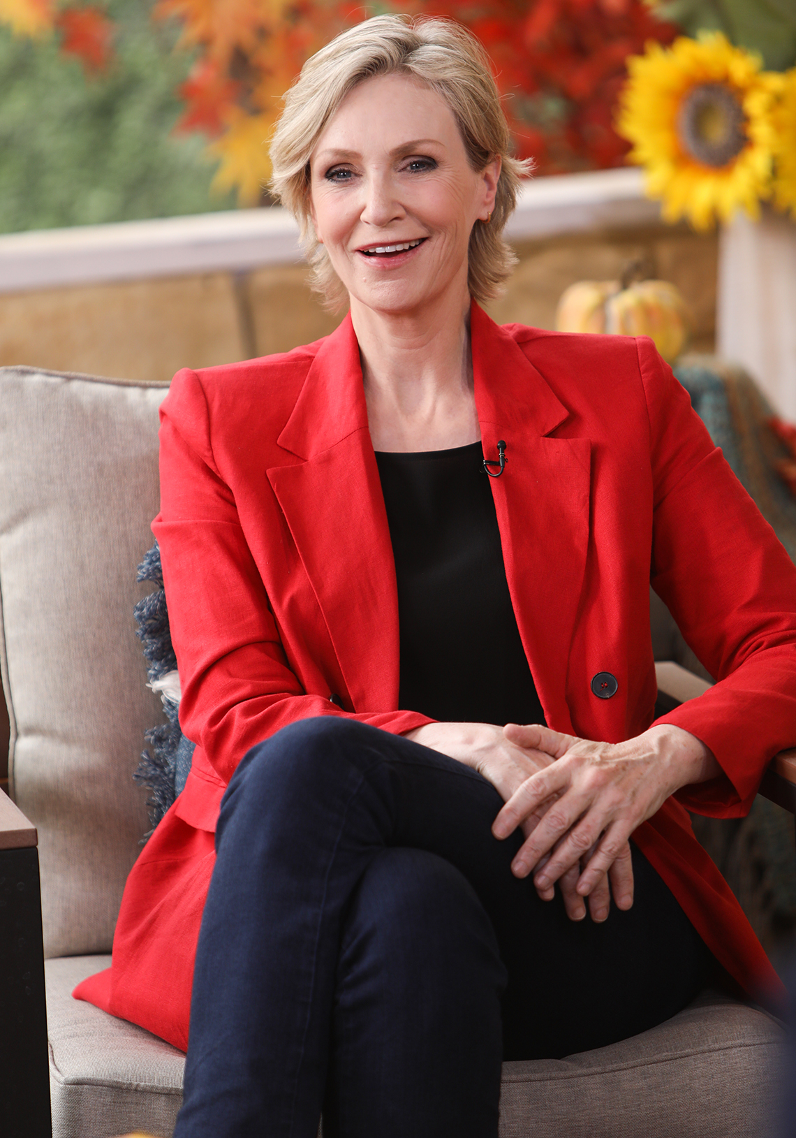 Actress Jane Lynch sitting in a chair in a fall-themed background setting