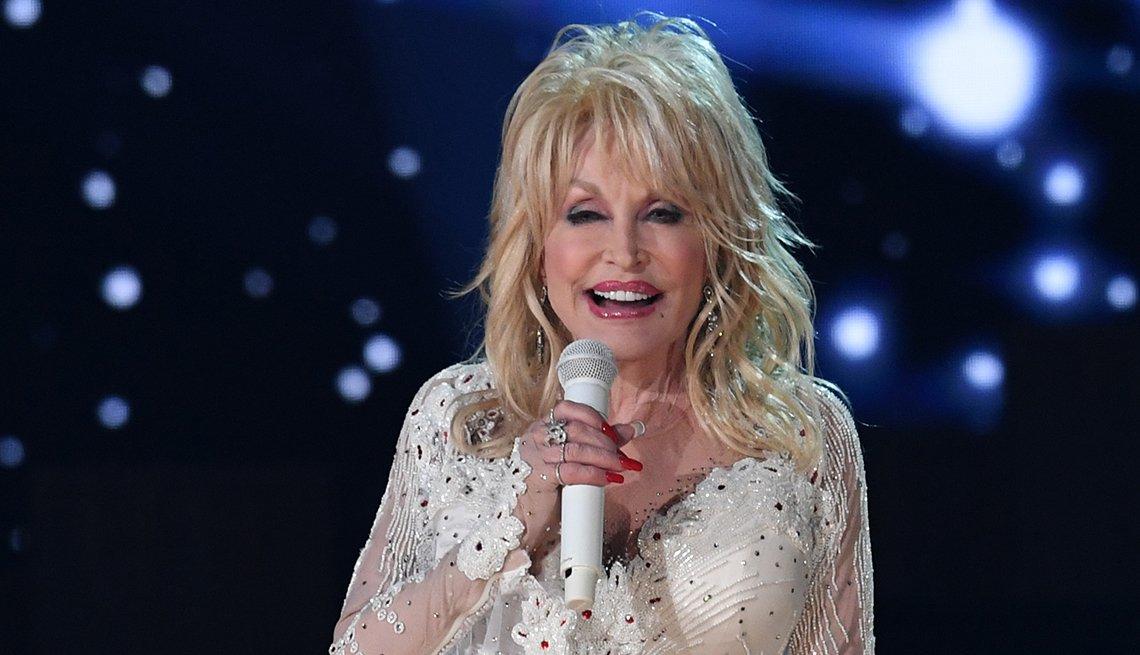 Dolly Parton sosteniendo un micrófono mientras actúa en el escenario.