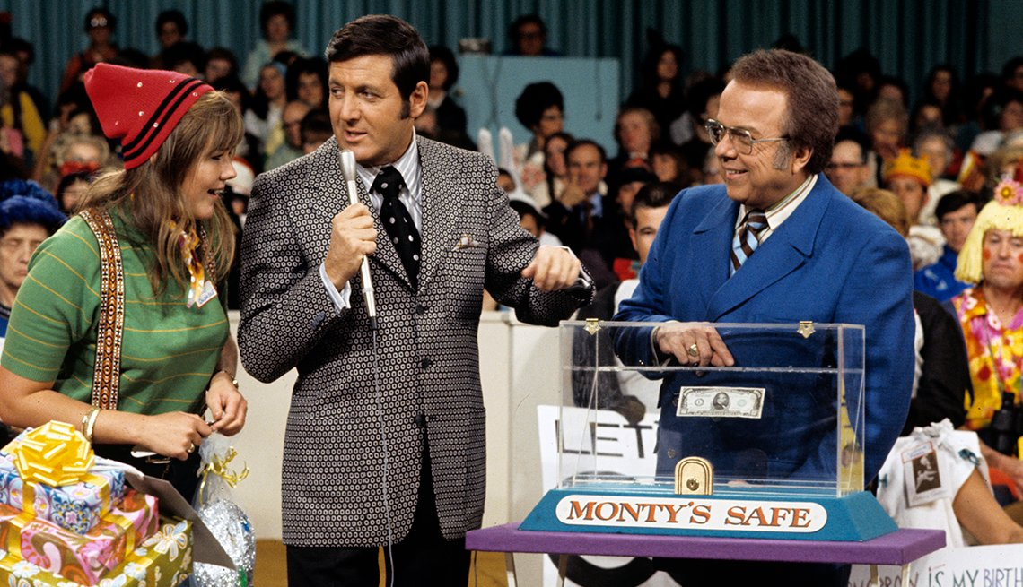 Let's Make a Deal host Monty Hall talks to a contestant as announcer Jay Stewart points to Monty's Safe