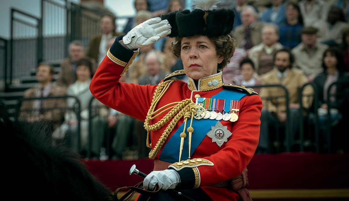 Olivia Coleman, starring as Queen Elizabeth II, gives a salute while riding a horse in a scene from The Crown