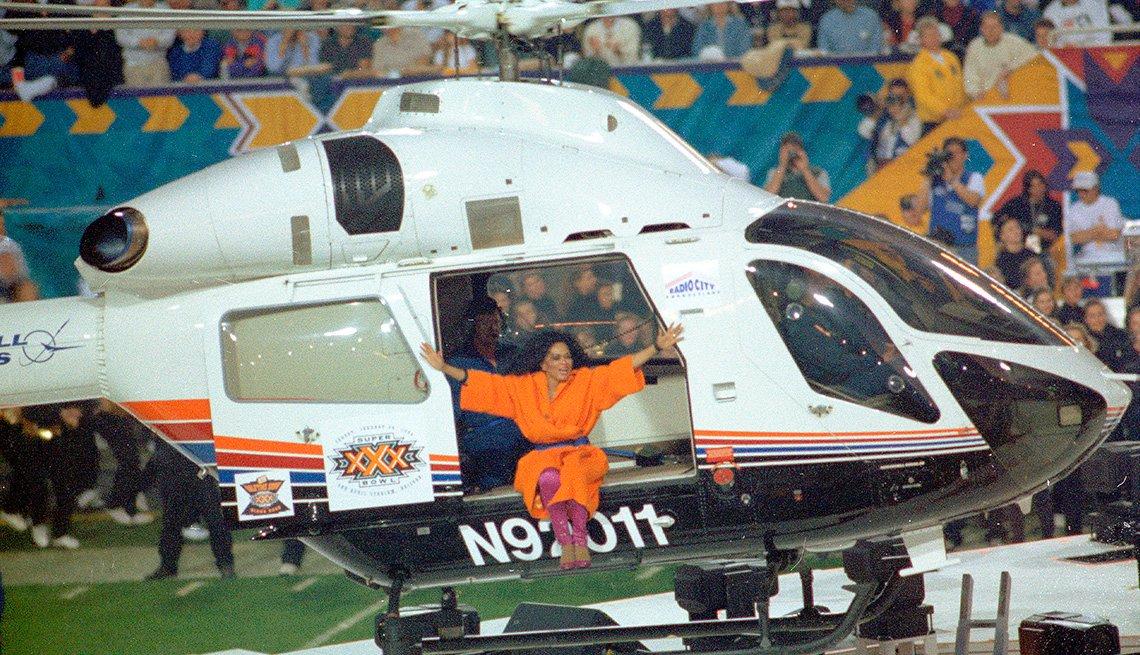 Diana Ross sentada en el borde de un helicóptero durante su actuación en el espectáculo de medio tiempo del Super Bowl XXX.