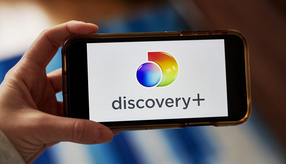 Una persona que sostiene un teléfono inteligente con el logotipo del servicio de transmisión Discovery Plus.