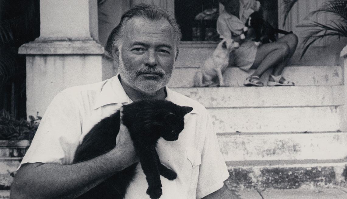 Ernest Hemingway sosteniendo un gato en su casa en Cuba.