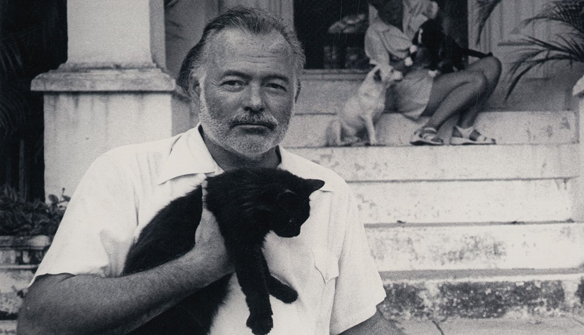 Ernest Hemingway holding a cat at his home in Cuba