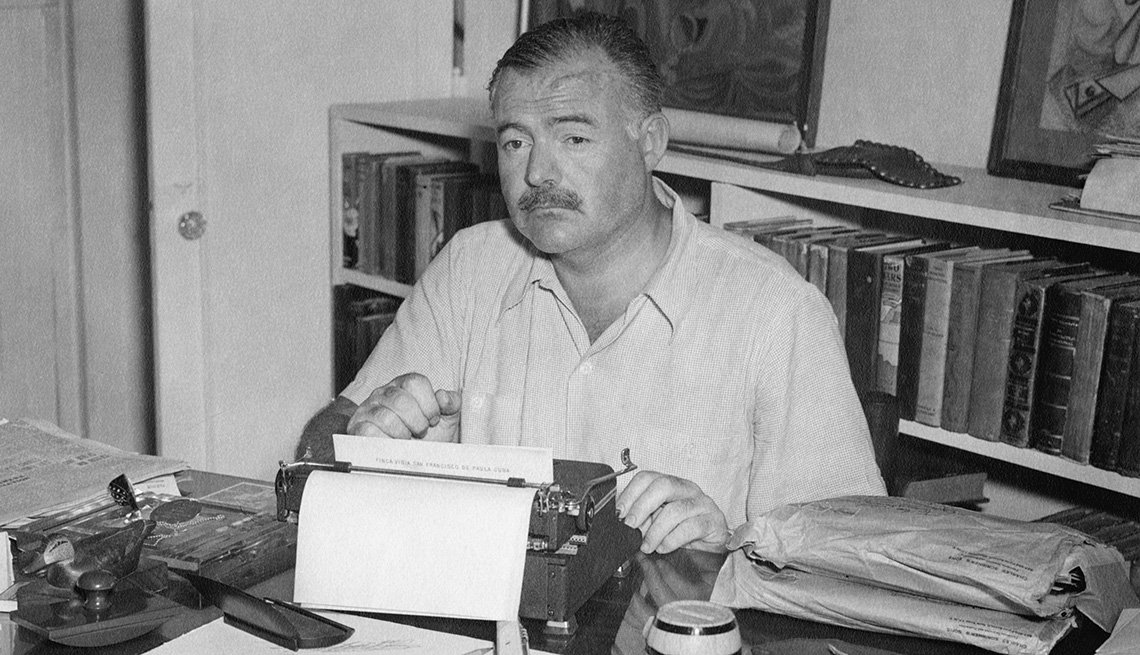 Ernest Hemingway sitting at typewriter at his home in Cuba