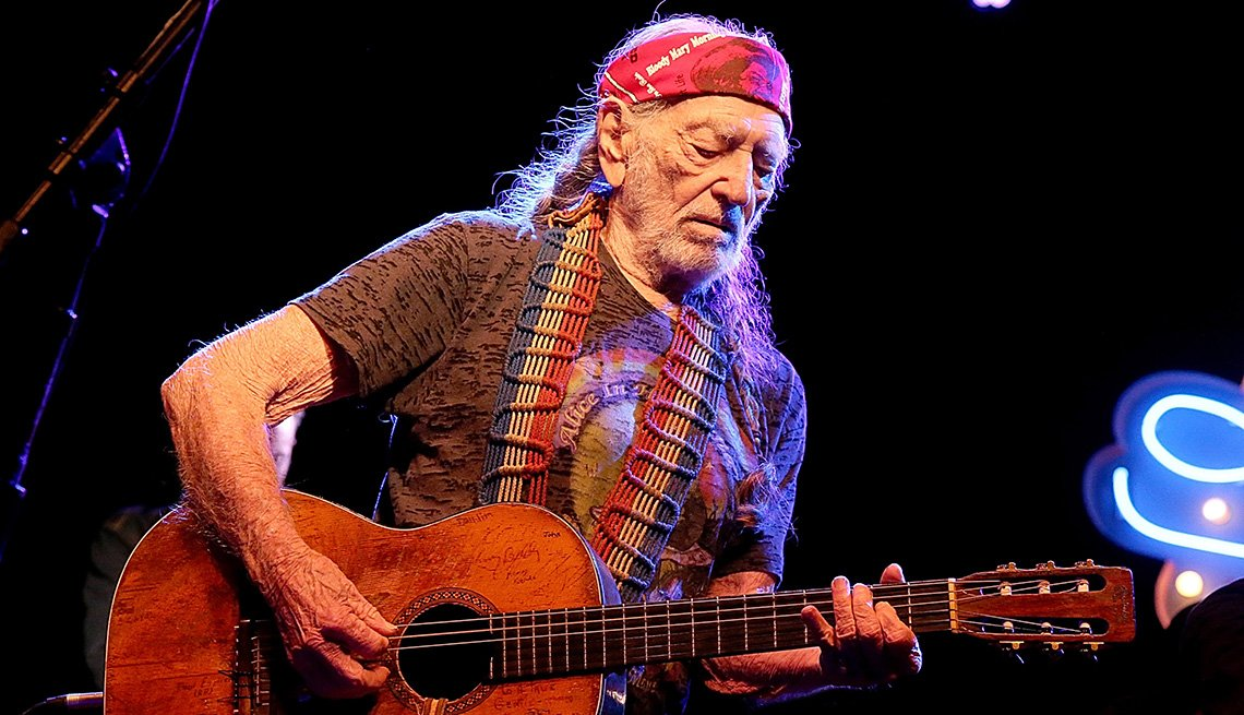 Willie Nelson playing his guitar in concert