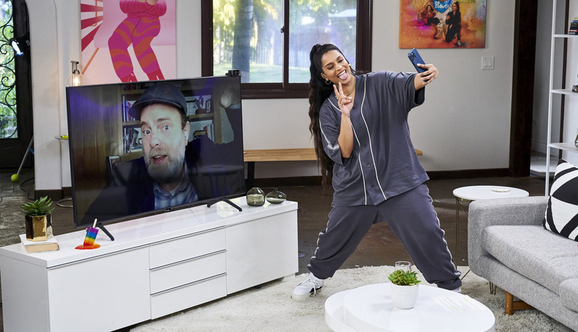 Lilly Singh taking a selfie with Rainn Wilson on a television monitor during a virtual interview on A Little Late With Lilly Singh