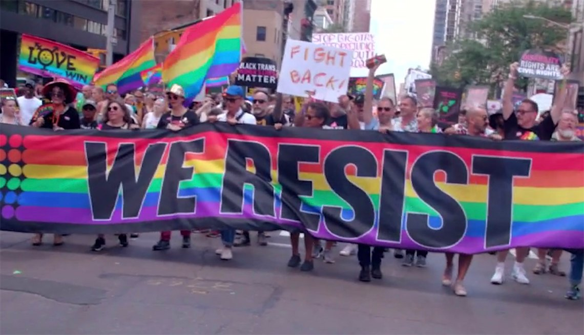 """A crowd at an LGBTQ rally holding a sign that says """"We Resist"""""""