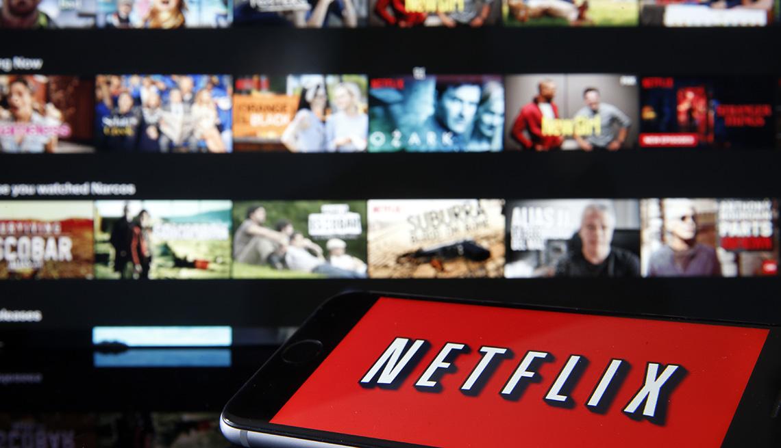 El logotipo de Netflix se muestra en un teléfono inteligente frente a una pantalla de televisión que se encuentra en la página de inicio del servicio de transmisión.