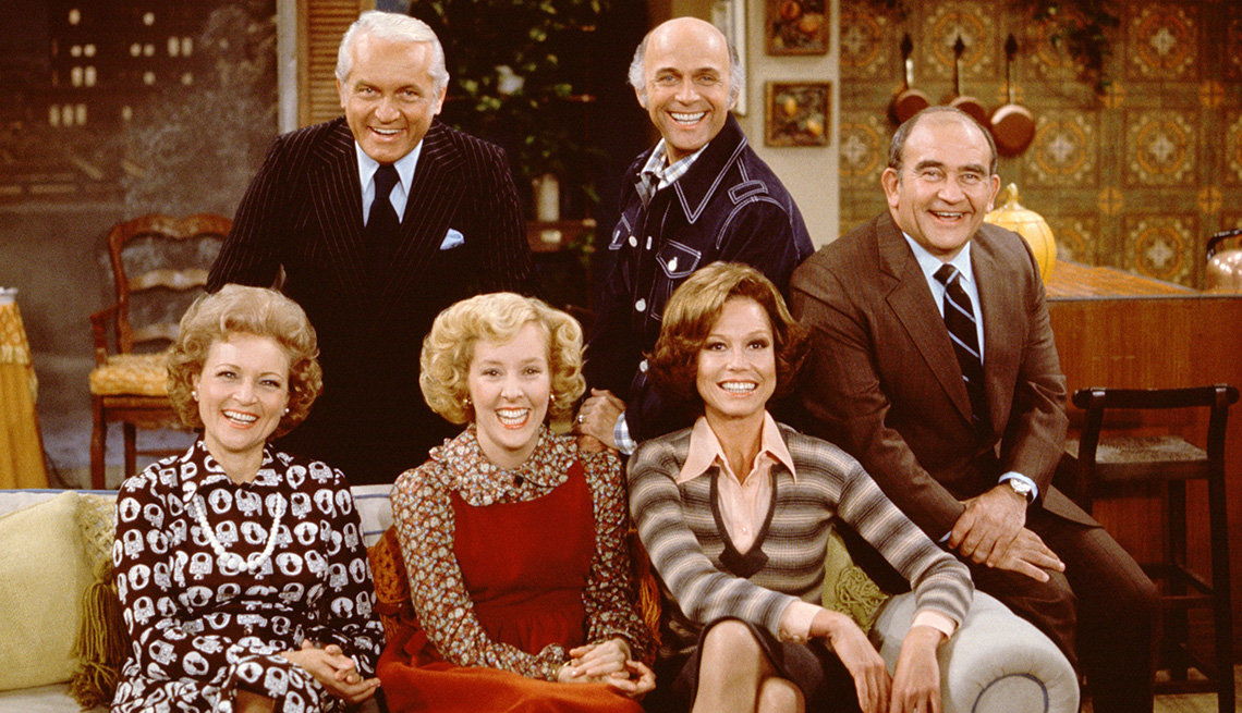 The cast of The Mary Tyler Moore Show sitting on a couch for a promotional photo