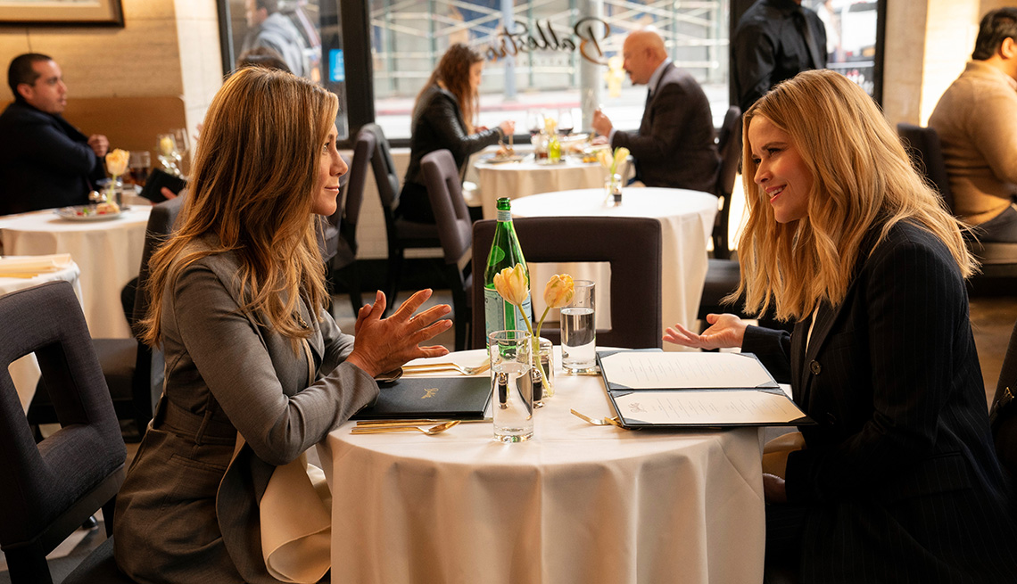 Jennifer Aniston and Reese Witherspoon sit at a restaurant table across from each other in a scene from The Morning Show