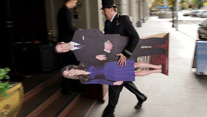 A hotel doorman in Melbourne, Australia, carries a life-size cutout of Prince William and Kate Middleton.
