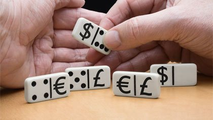 Unas manos organizan unas fichas de dominó con símbolos de dólar, euro y libra esterlina.