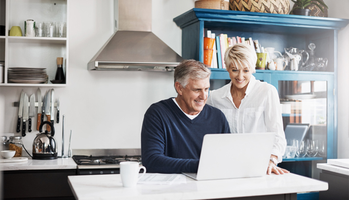 Man and woman at their kitchen table looking at a laptop screen